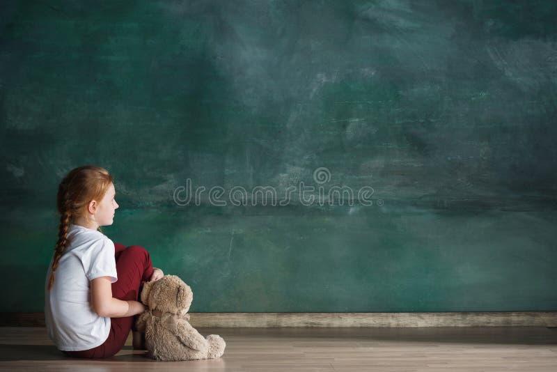 Meisje met teddybeerzitting op vloer in lege ruimte Autismeconcept stock afbeeldingen