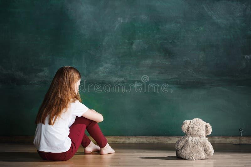 Meisje met teddybeerzitting op vloer in lege ruimte Autismeconcept royalty-vrije stock afbeeldingen