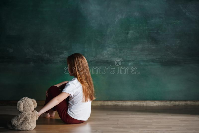 Meisje met teddybeerzitting op vloer in lege ruimte Autismeconcept royalty-vrije stock afbeelding