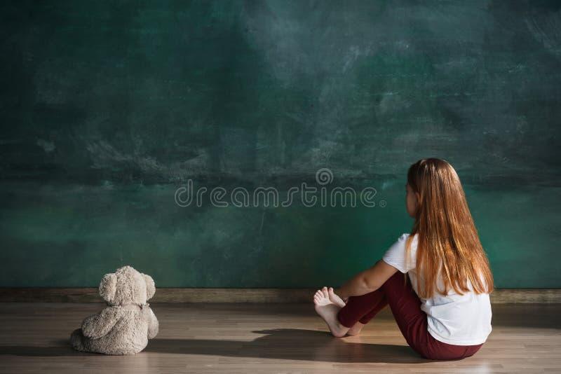 Meisje met teddybeerzitting op vloer in lege ruimte Autismeconcept stock afbeelding