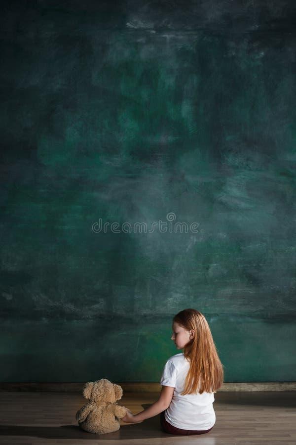 Meisje met teddybeerzitting op vloer in lege ruimte Autismeconcept stock foto