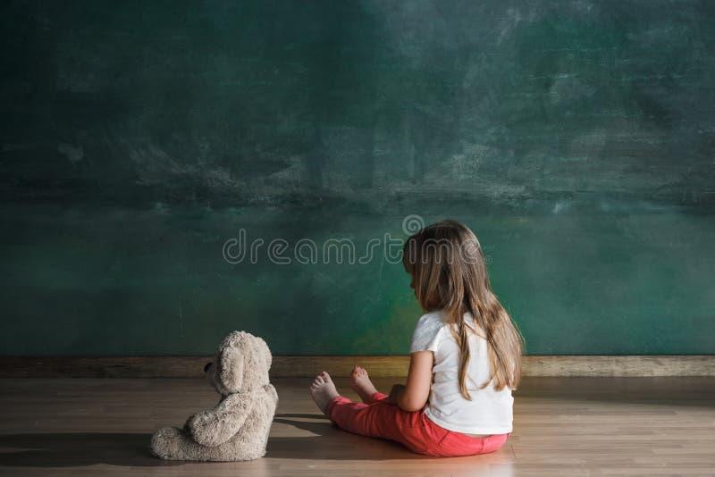 Meisje met teddybeerzitting op vloer in lege ruimte Autismeconcept royalty-vrije stock foto