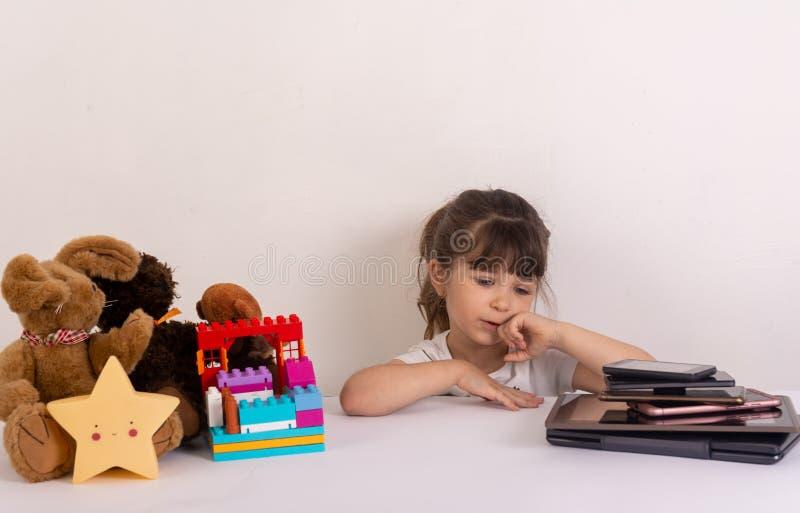 Meisje met telefoonsmobiele toepassingen wordt geobsedeerd die ouders en speelgoed negeren thuis, jong geitje dat gebruikend smar stock afbeelding