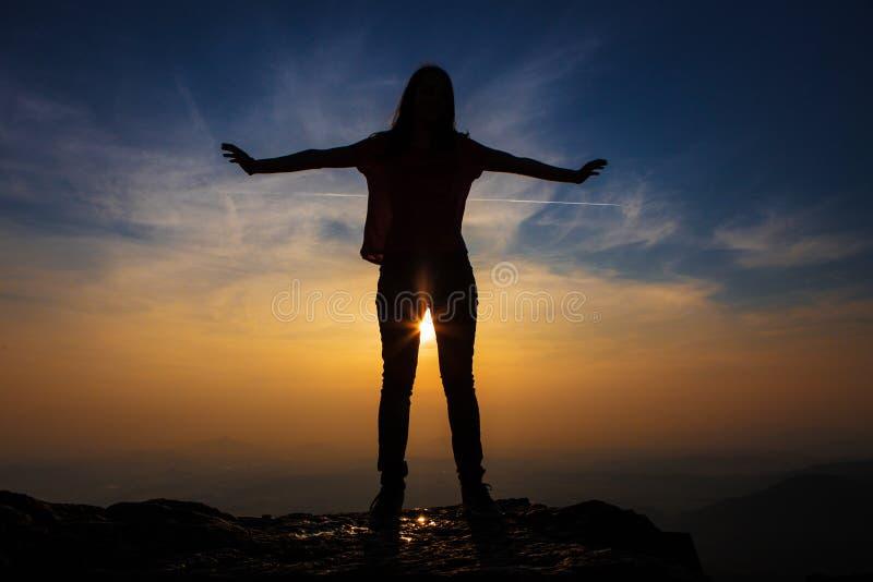 Meisje met uitgestrekte handen bij zonsondergangsilhouet royalty-vrije stock foto's