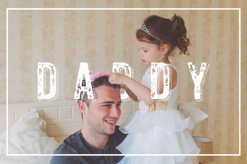 Meisje met vader die kronen dragen Het concept van de vadersdag stock foto