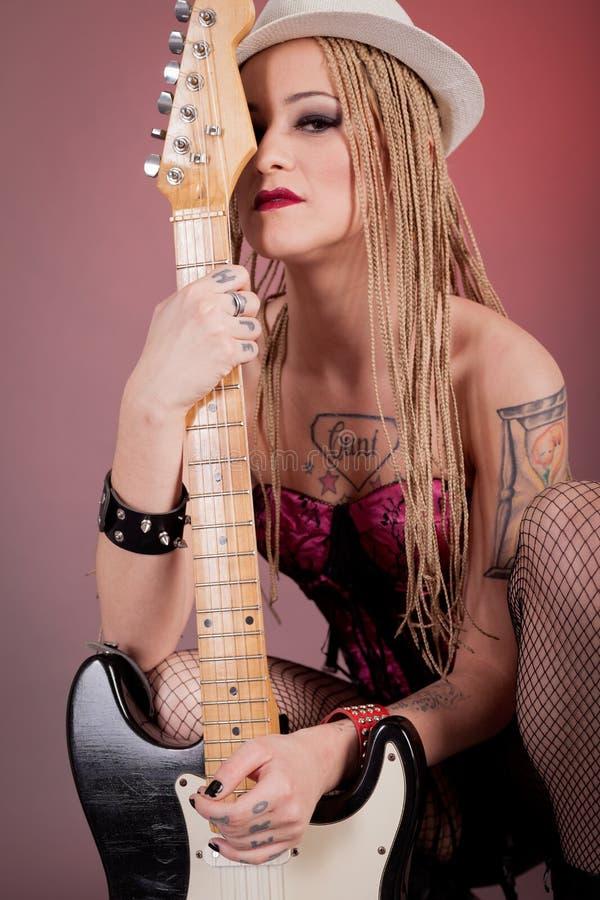 Meisje met veel tatoegeringen die met gitaar stellen stock afbeeldingen