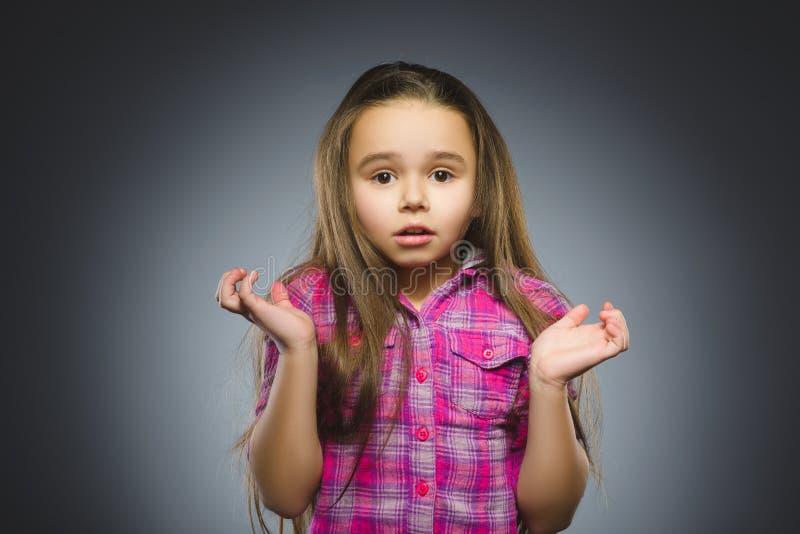 Meisje met verbaasde uitdrukking terwijl status tegen grijze achtergrond royalty-vrije stock afbeelding