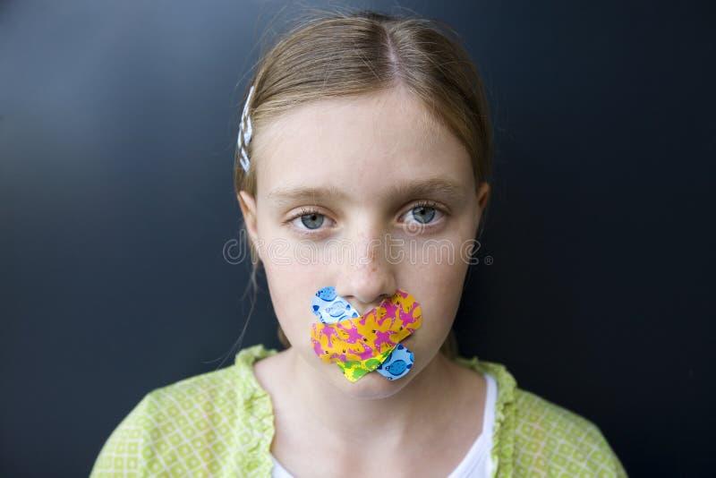 Meisje met verbanden over haar mond stock afbeeldingen