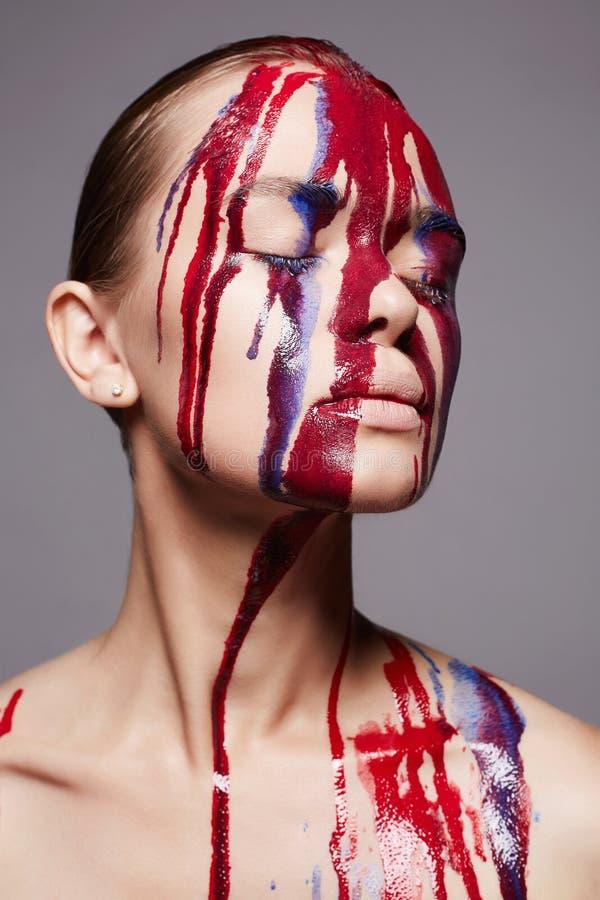 Meisje met verf op haar gezicht vloeibare verfstroom stock fotografie