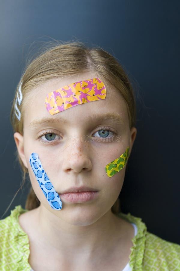 Meisje met verscheidene kleurrijke verbanden stock foto