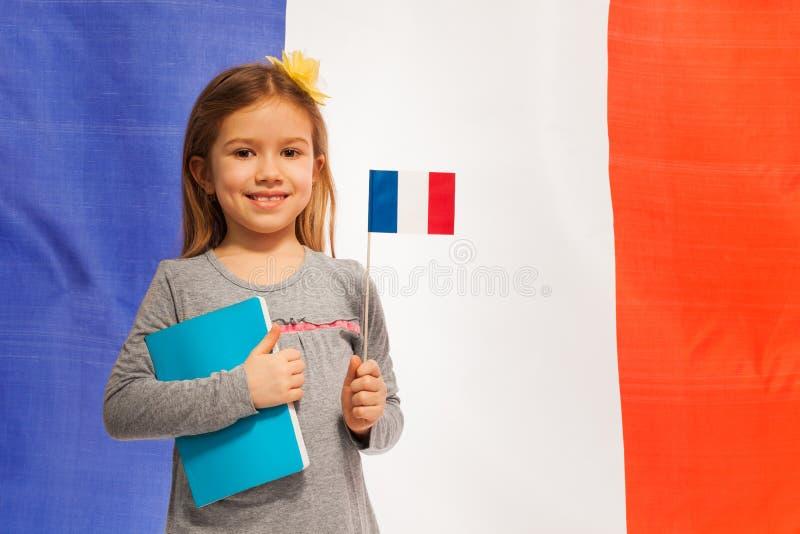 Meisje met vlag en boek tegen Franse banner stock foto's