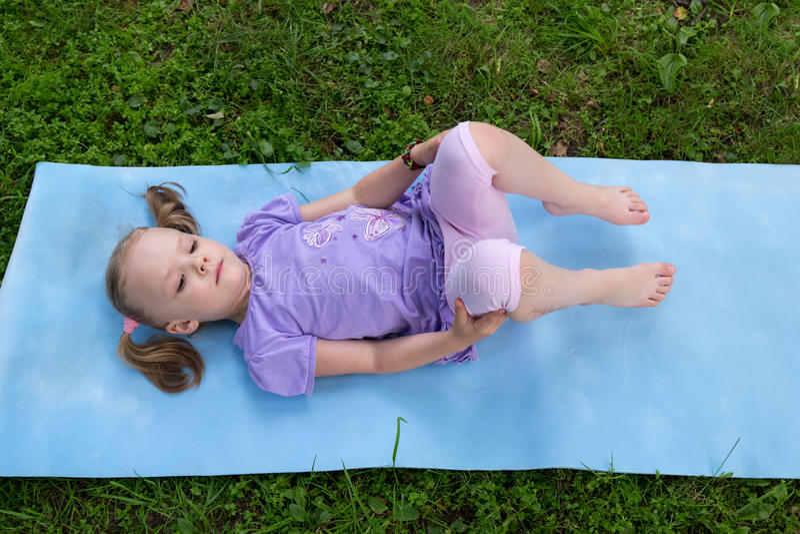 Meisje met vlechten die op een mat op gras liggen royalty-vrije stock foto