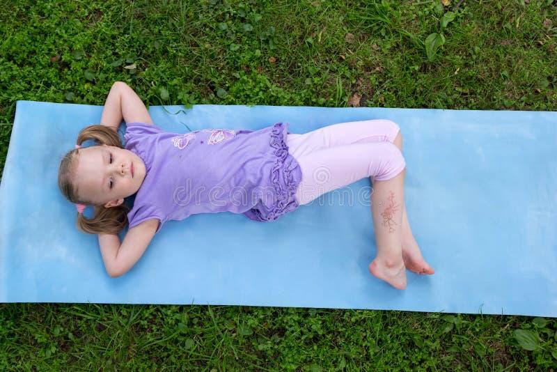 Meisje met vlechten die op een mat op gras liggen stock afbeeldingen