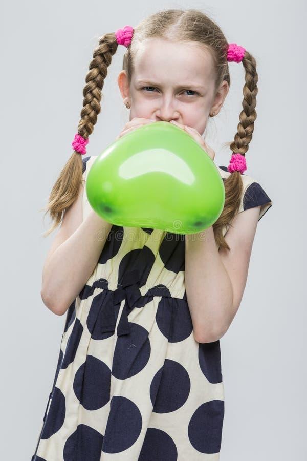 Meisje met Vlechten die in Polka Dot Dress Against White stellen Het blazen - omhoog Groene Hart Gevormde Luchtballon stock afbeelding