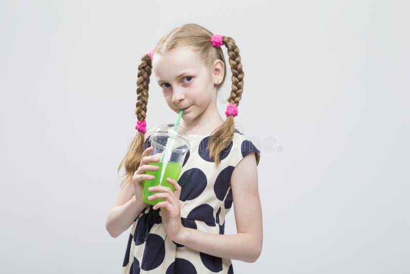 Meisje met Vlechten die in Polka Dot Dress met Kop van Groen Sap stellen stock afbeelding