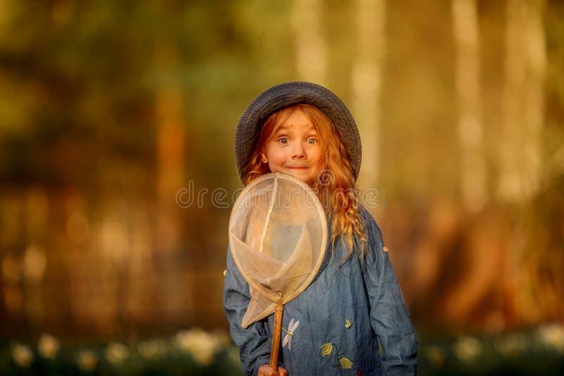 Meisje met vlinder netto openlucht bij zonsondergang royalty-vrije stock afbeeldingen
