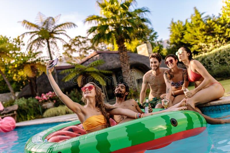 Meisje met vrienden die selfie bij poolpartij nemen royalty-vrije stock foto's