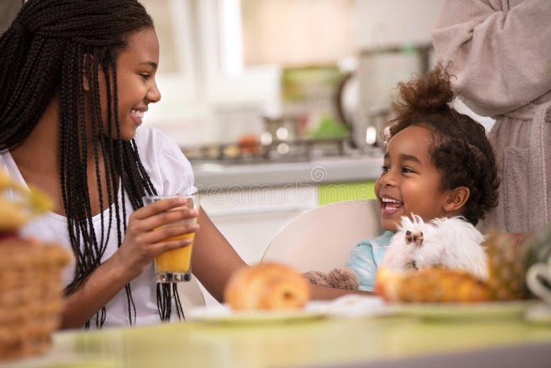 Meisje met weinig zuster bij de lijst die ontbijt hebben stock afbeelding
