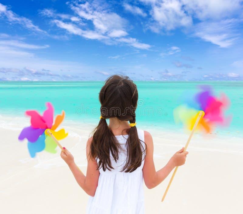 Meisje met windmolens op strand stock afbeeldingen
