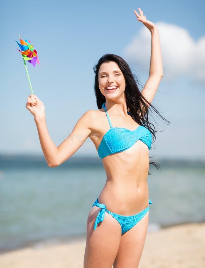Meisje met windmolenstuk speelgoed op het strand stock foto