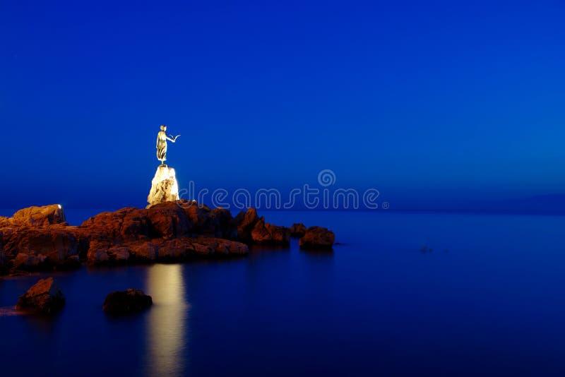 Meisje met zeemeeuw tijdens blauw uur stock fotografie