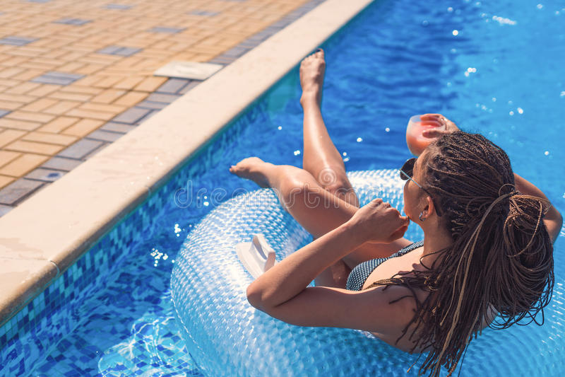 Meisje met zizi die cornrows dreadlocks in zwemmende cirkel liggen royalty-vrije stock foto's