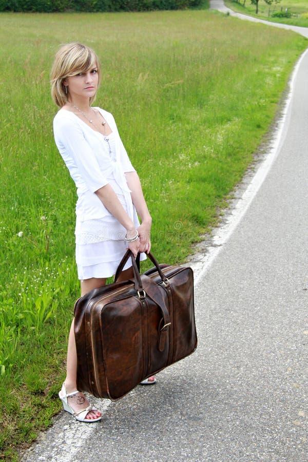 Meisje met zware koffer stock afbeeldingen