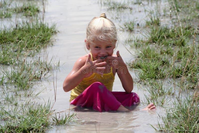 Meisje in modderig water royalty-vrije stock afbeeldingen