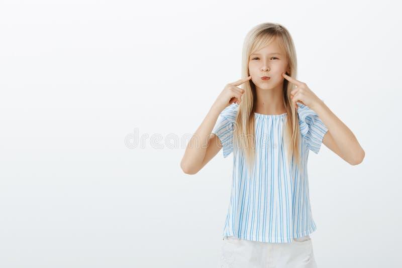 Meisje mokken, die als ballon kijken Portret die van leuke kinderachtige jonge blonde dochter in blauwe modieuze blouse, pruilen  royalty-vrije stock afbeelding