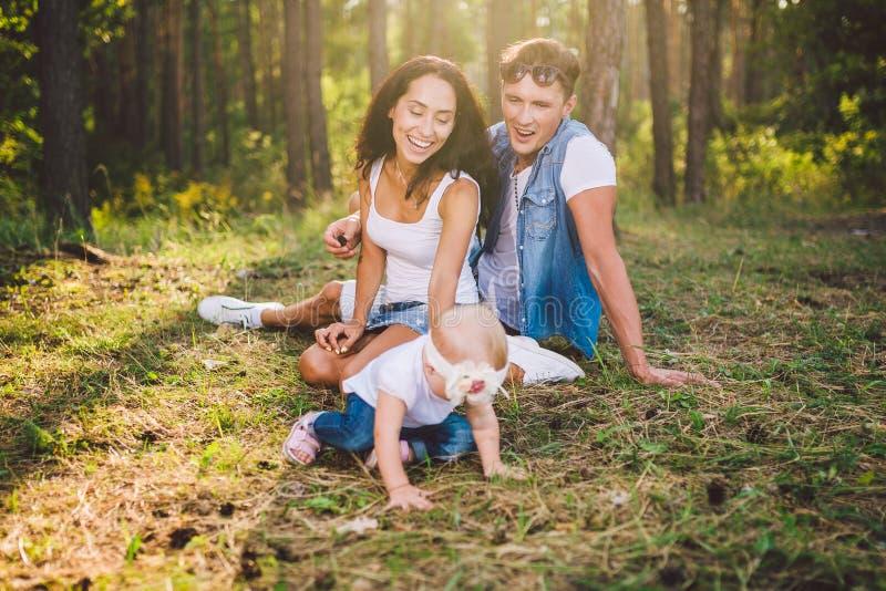 Meisje ??n jaar op de achtergrond van ouders rusten die op gras die op aard in het park leren te lopen liggen De eerste stappen royalty-vrije stock foto