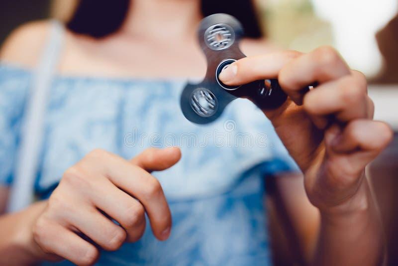 Meisje om met Fidget Spinner in zijn handen te spelen, het concept het verlichten van spanning stock afbeelding