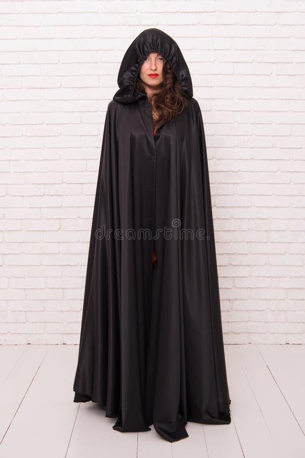 Meisje omvat met mantel duivelsconcept Halloween-maskerade De partij van Halloween Duivel van de vloek de mooie vrouw Dood in zwa royalty-vrije stock afbeelding