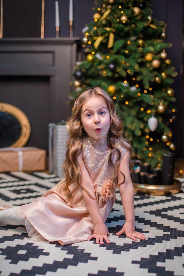 Meisje onder de Kerstboom Een meisje met giften onder de boom in afwachting van magisch royalty-vrije stock foto's