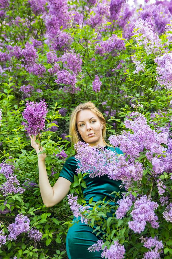 Meisje op de achtergrond van een bloeiende lilac boom royalty-vrije stock foto