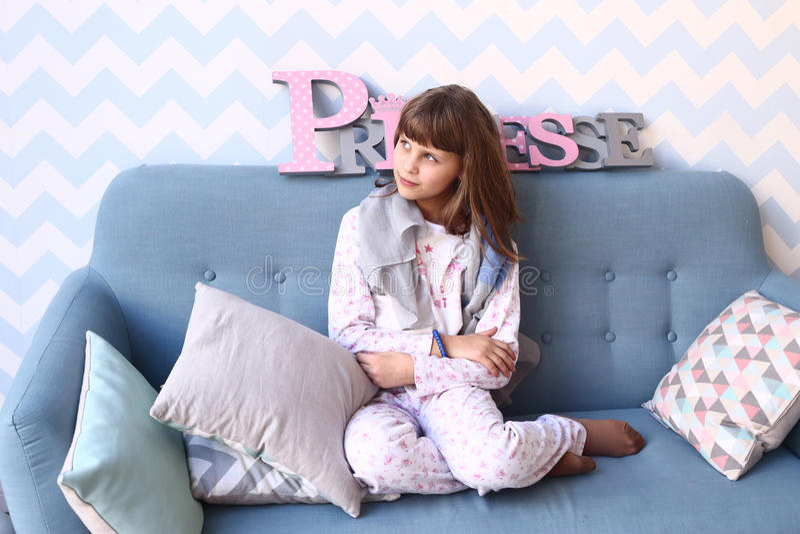 Meisje op de bank in pyjama's met hoofdkussens stock fotografie