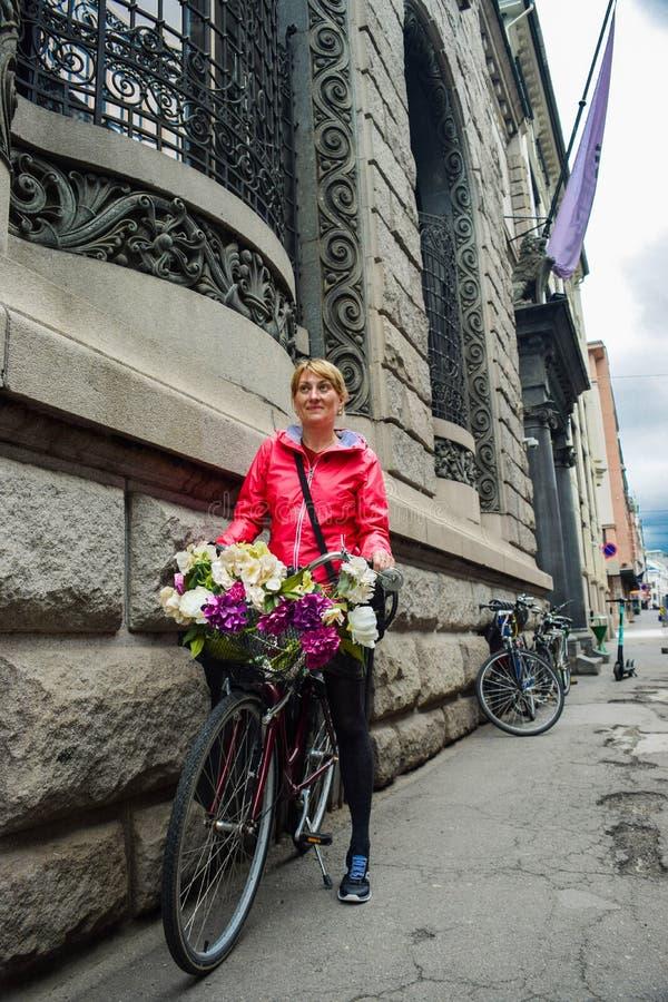 Meisje op de fiets, versierd met bloemen stock foto's
