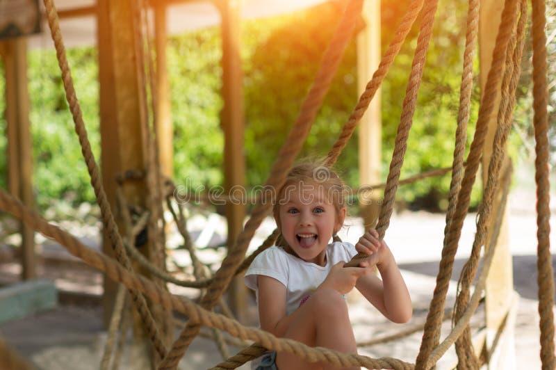 Meisje op de hinderniscursus, hoge kabelscursus, de zomer, vreugde, gezondheid, goedemorgen stock afbeelding