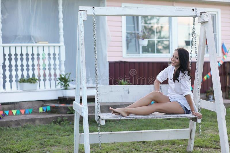 Meisje op de houten portiek dichtbij het huis royalty-vrije stock foto