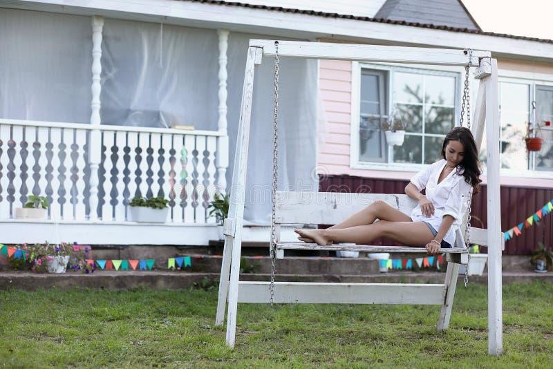 Meisje op de houten portiek dichtbij het huis royalty-vrije stock afbeelding