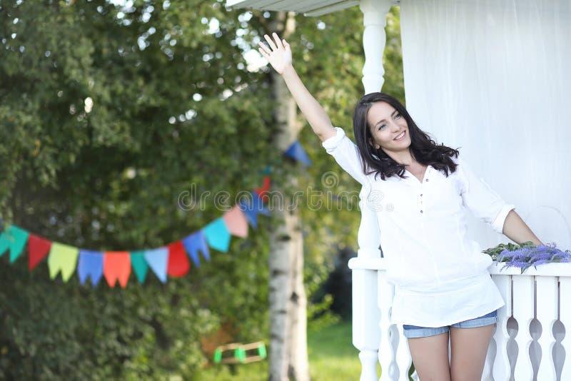 Meisje op de houten portiek dichtbij het huis royalty-vrije stock foto's