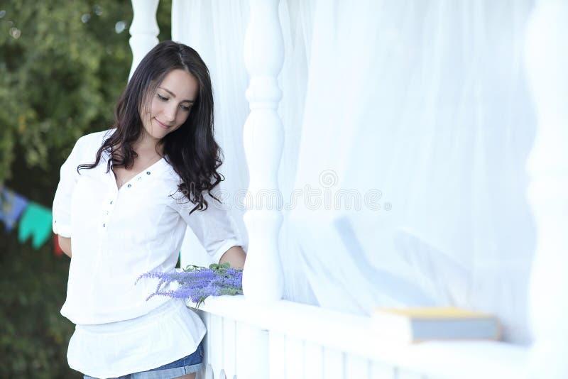 Meisje op de houten portiek dichtbij het huis stock afbeeldingen