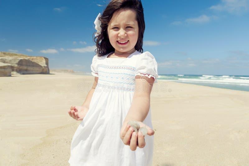 Meisje op de stenen van de strandholding royalty-vrije stock fotografie
