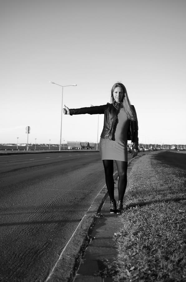 Meisje op de weg die op een auto wacht stock foto