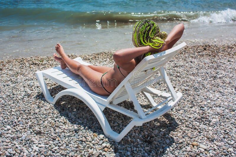 Meisje op de witte chaise zitkamer op het strand royalty-vrije stock foto's