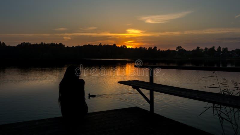 Meisje op een brug tijdens zonsondergang stock foto
