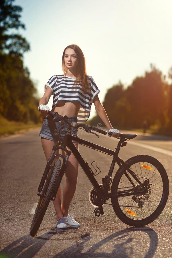 Meisje op een fiets bij zonsondergang royalty-vrije stock foto's
