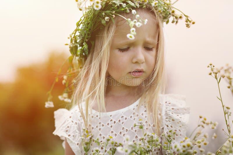 Meisje op een gang op een heldere de zomerdag Portret van een klein meisje met een kroon van kamilles op haar hoofd stock fotografie
