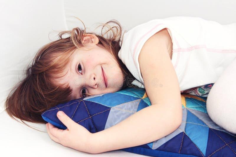 Meisje op een kleurrijk hoofdkussen stock foto