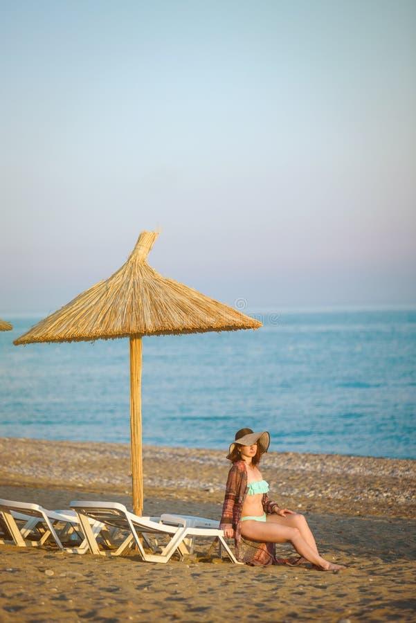 Meisje op een strand, onder een strandparaplu stock foto