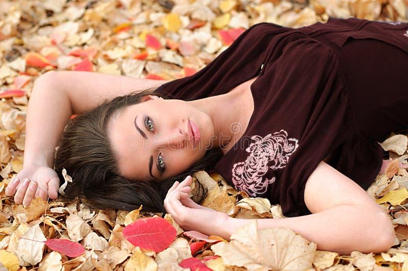 Meisje op een tapijt van bladeren stock fotografie